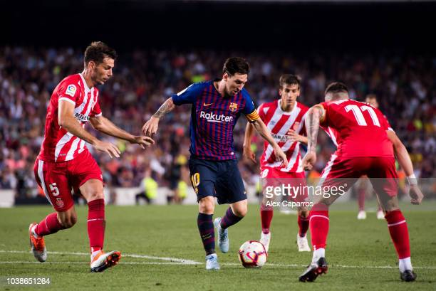 Lionel Messi of FC Barcelona conducts the ball under pressure from Pedro Alcala and Francisco Aday of Girona FC during the La Liga match between FC...