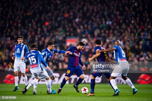 Lionel Messi of FC Barcelona conducts the ball under pressure from Javi Fuego and David Lopez of RCD Espanyol during the Spanish Copa del Rey Quarter...