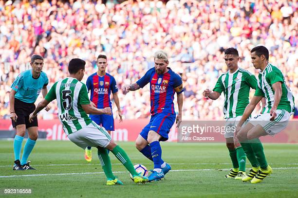 Lionel Messi of FC Barcelona conducts the ball with the opposition of Petros Matheus of Real Betis Balompie during the La Liga match between FC...