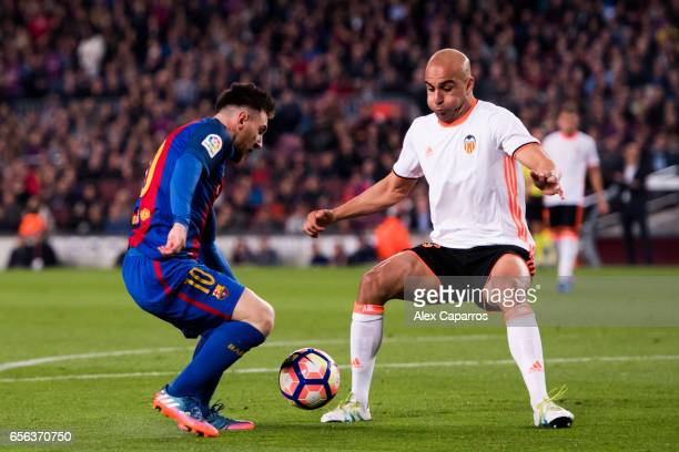 Lionel Messi of FC Barcelona dribbles Aymen Abdennour of Valencia CF before scoring his team's third goal during the La Liga match between FC...