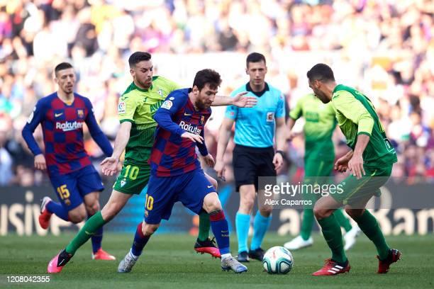 Lionel Messi of FC Barcelona dribbles Edu Exposito and Esteban Burgos of SD Eibar during the La Liga match between FC Barcelona and SD Eibar SAD at...