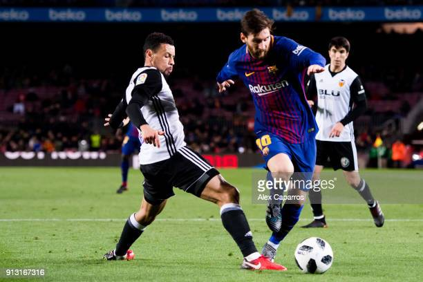 Lionel Messi of FC Barcelona dribbles Francis Coquelin of Valencia CF to assist his teammate Luis Suarez to score the opening goal during the Copa...