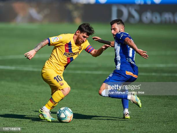 Lionel Messi of FC Barcelona dribbles Luis Rioja of Deportivo Alaves during the Liga match between Deportivo Alaves and FC Barcelona at Estadio de...