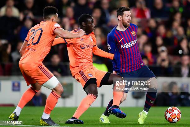Lionel Messi of FC Barcelona dribbles past Ferland Mendy and Fernando Marçal of Olympique Lyonnais during the UEFA Champions League Round of 16...