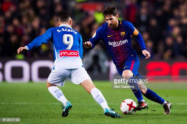 Lionel Messi of FC Barcelona dribbles Sergio Garcia of RCD Espanyol during the Spanish Copa del Rey Quarter Final Second Leg match between FC...