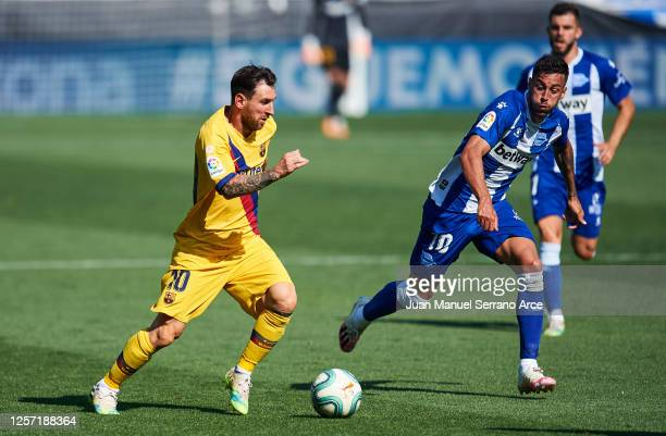Lionel Messi of FC Barcelona dribbles Victor Camarasa of Deportivo Alaves during the Liga match between Deportivo Alaves and FC Barcelona at Estadio...