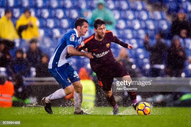 Lionel Messi of FC Barcelona dribbles Victor Sanchez of RCD Espanyol during the La Liga match between Espanyol and Barcelona at RCDE Stadium on...