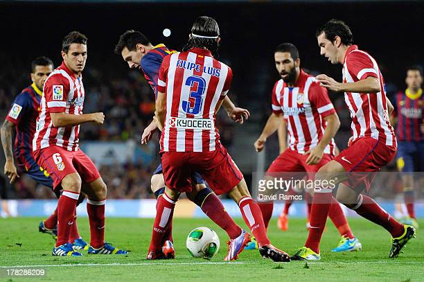 Lionel Messi of FC Barcelona duels for the ball among Atletico de Madrid players during the Spanish Super Cup second leg match between FC Barcelona...
