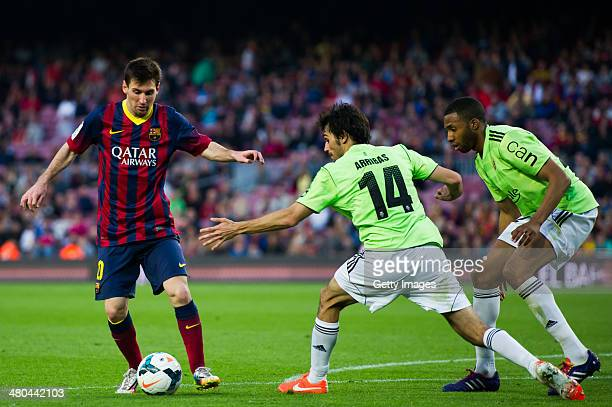 Lionel Messi of FC Barcelona duels for the ball with Alejandro Arribas and Jordan Loties of CA Osasuna during the La Liga match between FC Barcelona...