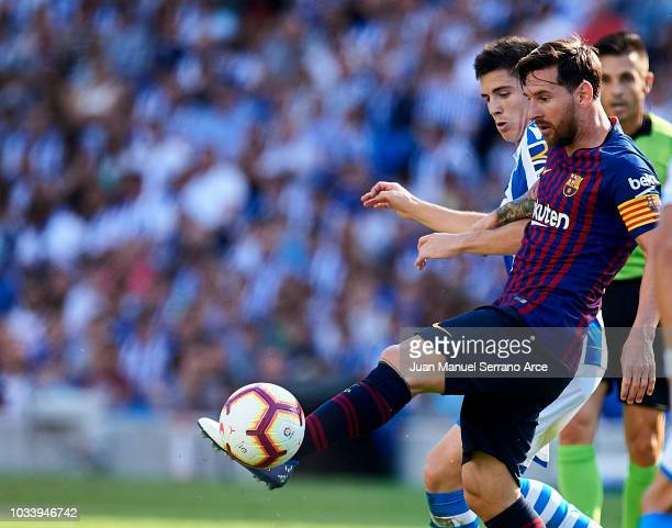 Lionel Messi of FC Barcelona duels for the ball with Aritz Elustondo of Real Sociedad during the La Liga match between Real Sociedad de Futbol and FC...