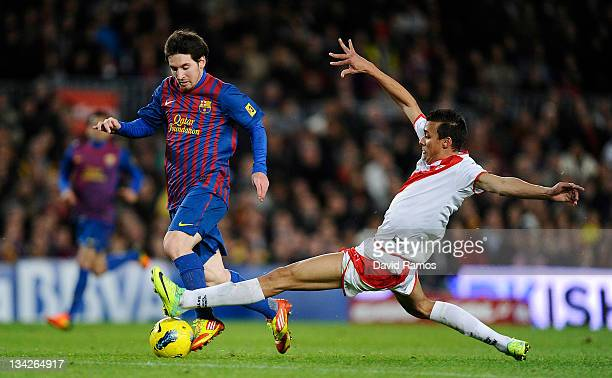 Lionel Messi of FC Barcelona duels for the ball with Botelho of Rayo Vallecano during the La Liga match between FC Barcelona and Rayo Vallecano at...