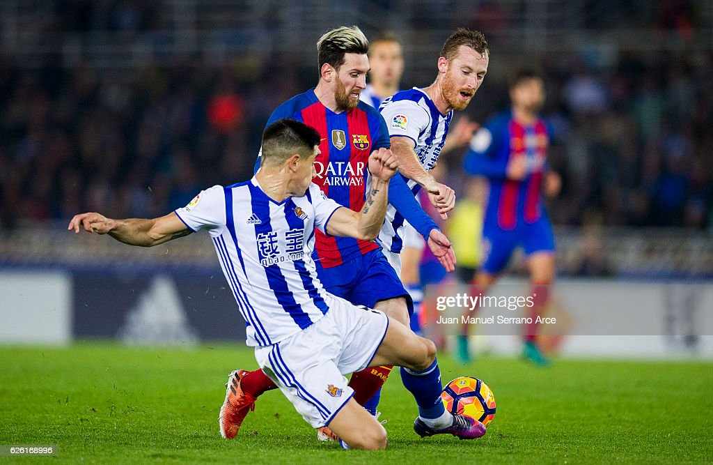 Lionel Messi of FC Barcelona duels for the ball with David Zurutuza and Yuri Berchiche of Real Sociedad during the La Liga match between Real Sociedad de Futbol and FC Barcelona at Estadio Anoeta on November 27, 2016 in San Sebastian, Spain.