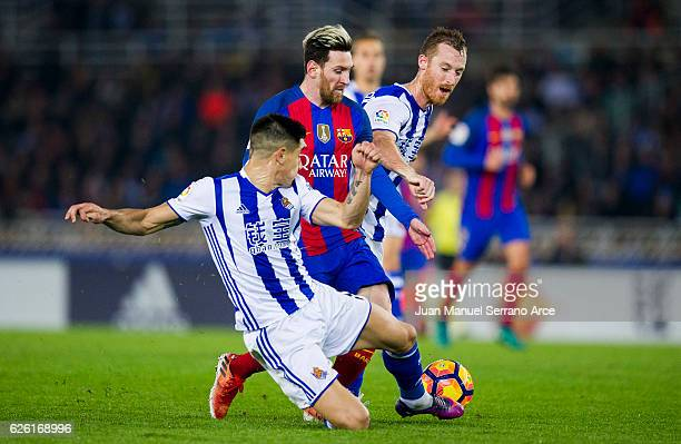 Lionel Messi of FC Barcelona duels for the ball with David Zurutuza and Yuri Berchiche of Real Sociedad during the La Liga match between Real...