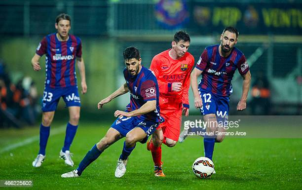 Lionel Messi of FC Barcelona duels for the ball with Didac Vila of SD Eibar during the La Liga match between SD Eibar and FC Barcelona at Ipurua...