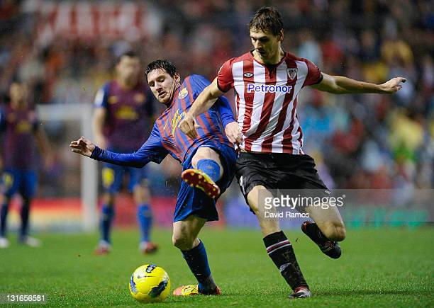 Lionel Messi of FC Barcelona duels for the ball with Fernando Llorente of Athletic Club during the La Liga match between Athletic Club and FC...