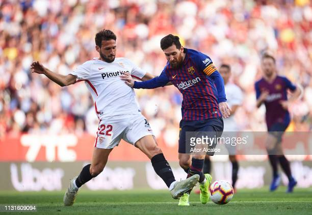 Lionel Messi of FC Barcelona duels for the ball with Franco Vazquez of Sevilla FC during the La Liga match between Sevilla FC and FC Barcelona at...