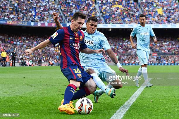 Lionel Messi of FC Barcelona duels for the ball with Juan Carlos Perez of Granda CF during the La Liga match between FC Barcelona and Granada CF at...