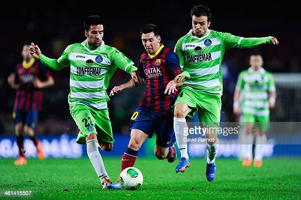 Lionel Messi of FC Barcelona duels for the ball with Juan Rodriguez and Pedro Leon of Getafe CF during the Copa del Rey round of 16 first leg match...