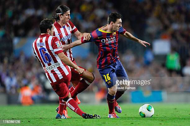 Lionel Messi of FC Barcelona duels for the ball with Koke Resurreccion and Filipe Luis of Atletico de Madrid during the Spanish Super Cup second leg...