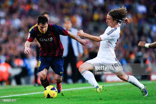 Lionel Messi of FC Barcelona duels for the ball with Luka Modric of Real Madrid CF during the La Liga match between FC Barcelona and Real Madrid CF...