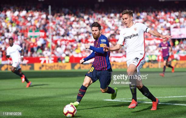 Lionel Messi of FC Barcelona duels for the ball with Marko Rog of Sevilla FC during the La Liga match between Sevilla FC and FC Barcelona at Estadio...