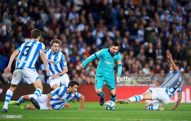 Lionel Messi of FC Barcelona duels for the ball with Mikel Merino of Real Sociedad during the Liga match between Real Sociedad and FC Barcelona at...