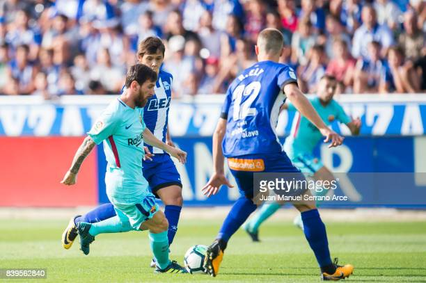 Lionel Messi of FC Barcelona duels for the ball with Oscar Romero of Deportivo Alaves during the La Liga match between Deportivo Alaves and Barcelona...