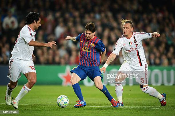 Lionel Messi of FC Barcelona duels for the ball with Philippe Mexes and Alessandro Nesta of AC Milan during the Champions League quarterfinal second...