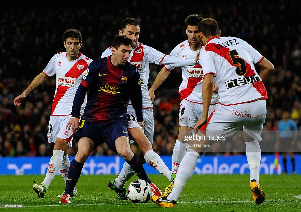Lionel Messi of FC Barcelona duels for the ball with Rayo Vallecano players during the La Liga match between FC Barcelona and Rayo Vallecano at Camp Nou on March 17, 2013 in Barcelona, Spain.