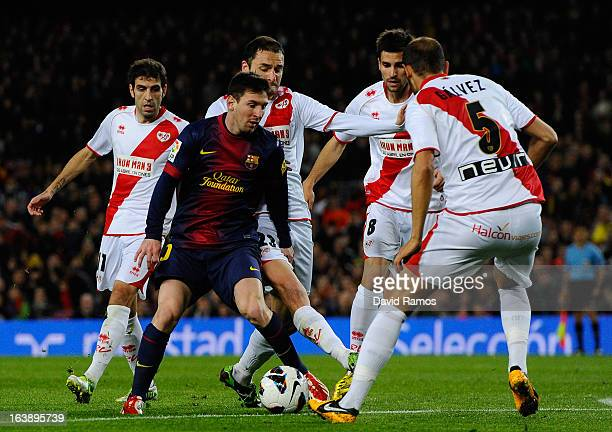 Lionel Messi of FC Barcelona duels for the ball with Rayo Vallecano players during the La Liga match between FC Barcelona and Rayo Vallecano at Camp...