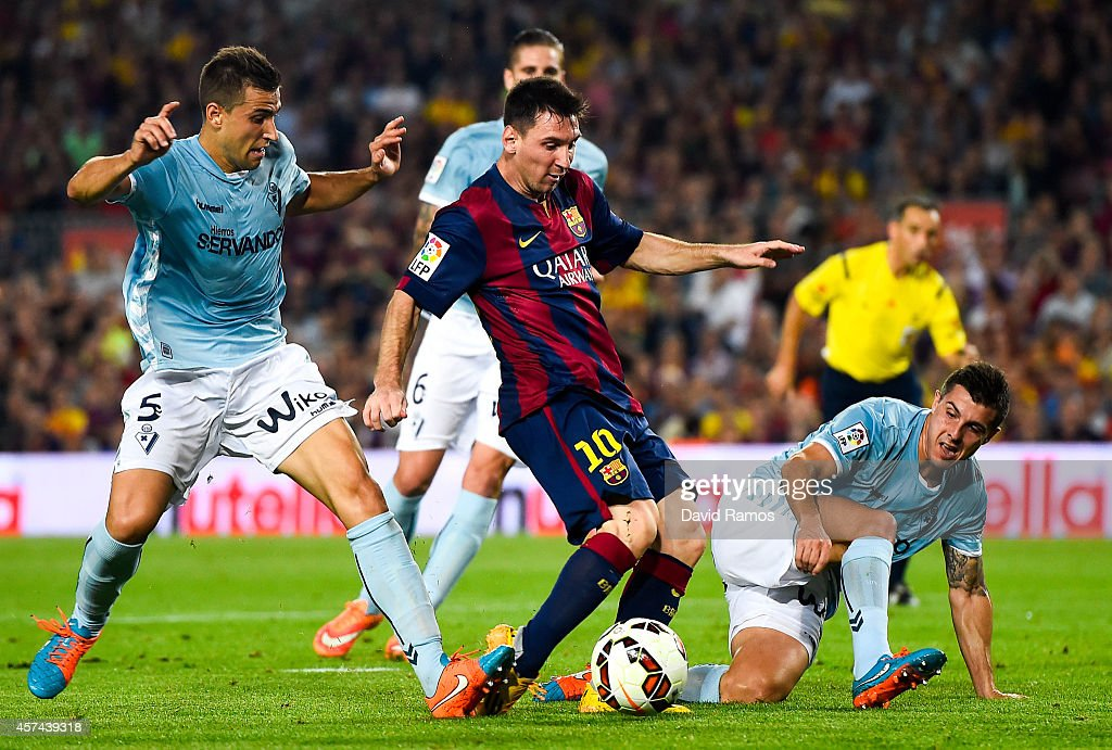 Lionel Messi of FC Barcelona duels for the ball with SD Eibar players during the La Liga match between FC Barcelona and SD Eibar at Camp Nou on October 18, 2014 in Barcelona, Spain.