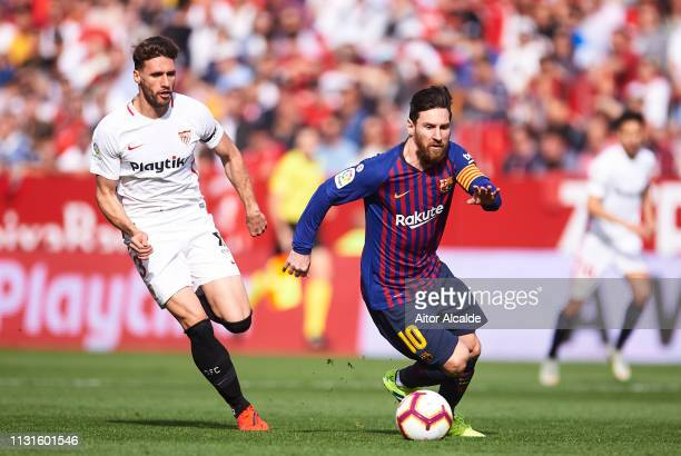Lionel Messi of FC Barcelona duels for the ball with Sergi Gomez of Sevilla FC during the La Liga match between Sevilla FC and FC Barcelona at...