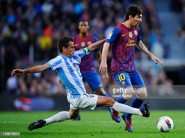 Lionel Messi of FC Barcelona duels for the ball with Sergio Duda of Malaga CF during the La Liga match between FC Barcelona and Malaga CF at Camp Nou...
