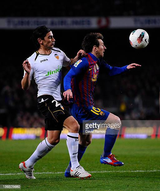 Lionel Messi of FC Barcelona duels for the ball with Tino Costa of Valencia CF during the La Liga match between FC Barcelona and Valencia CF at Camp...