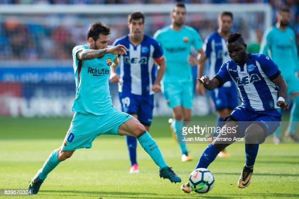 Lionel Messi of FC Barcelona duels for the ball with Wakaso Mubarak of Deportivo Alaves during the La Liga match between Deportivo Alaves and...