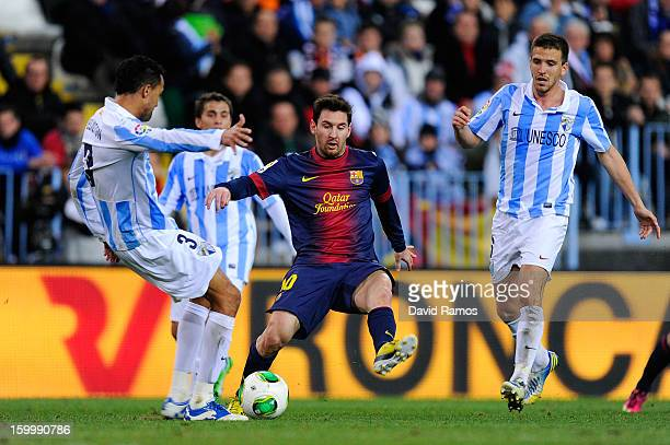 Lionel Messi of FC Barcelona duels for the ball with Welligton Robson and Ignacio Camacho of Malaga CF during the Copa del Rey Quarter Final 2nd leg...