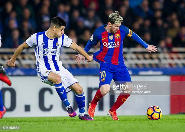 Lionel Messi of FC Barcelona duels for the ball with Yuri Berchiche of Real Sociedad during the La Liga match between Real Sociedad de Futbol and FC...