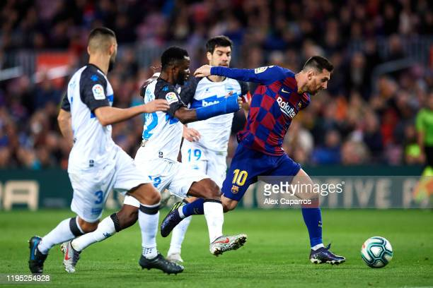 Lionel Messi of FC Barcelona eludes the pressure from Ruben Duarte, Wakaso Mubarak and Manu Garcia of Deportivo Alaves to score his team's third goal...
