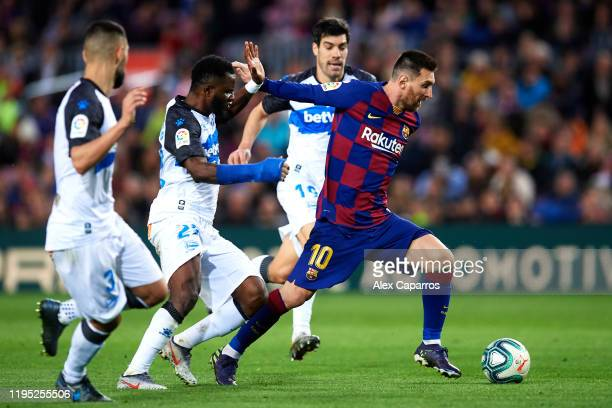 Lionel Messi of FC Barcelona eludes the pressure from Ruben Duarte Wakaso Mubarak and Manu Garcia of Deportivo Alaves to score his team's third goal...