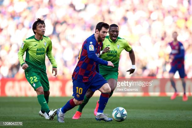 Lionel Messi of FC Barcelona eludes the pressure from Takashi Inui and Pape Diop of SD Eibar during the La Liga match between FC Barcelona and SD...