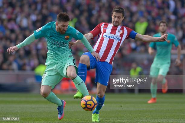 Lionel Messi of FC Barcelona fights for the ball with Gabi Fernandez of Atletico de Madrid during the La Liga match between Atletico Madrid and FC...