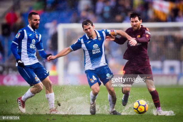 Lionel Messi of FC Barcelona fights for the ball with Victor Sanchez and Sergi Darder of RCD Espanyol during the La Liga match between Espanyol and...
