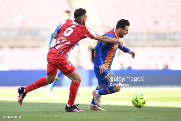 Lionel Messi of FC Barcelona gets away from Koke of Atletico Madrid during the La Liga Santander match between FC Barcelona and Atletico de Madrid at...