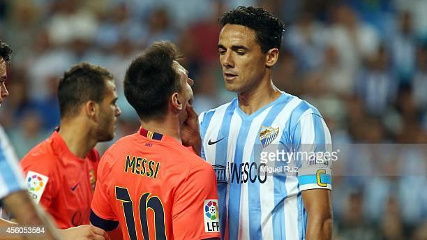 Lionel Messi of FC Barcelona gets fouled by Welingon of Malaga CF during the La Liga match between Malaga CF and FC Barcelona at La Rosaleda Stadium...