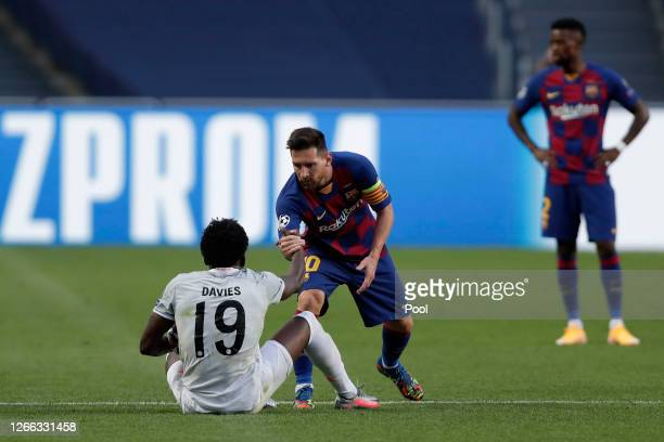 Lionel Messi of FC Barcelona helps Alphonso Davies of FC Bayern Munich to his feet after a challenge during the UEFA Champions League Quarter Final...