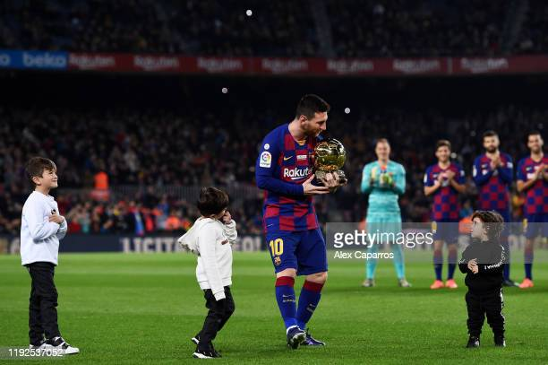 Lionel Messi of FC Barcelona holds his sixth Ballon d'Or trophy as his children Ciro Messi Roccuzzo Thiago Messi Roccuzzo and Mateo Messi Roccuzzo...