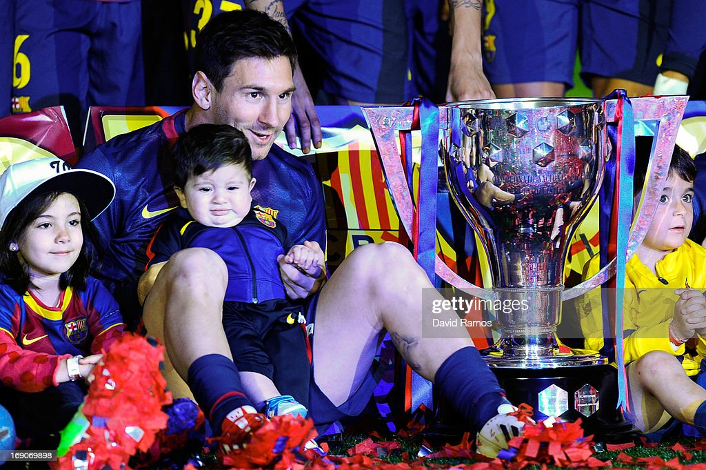 Lionel Messi of FC Barcelona holds his son Thiago as they sit next to the trophy during the celebration after winning the Spanish League after the La Liga match between FC Barcelona and Real Valladolid CF at Camp Nou on May 19, 2013 in Barcelona, Spain.