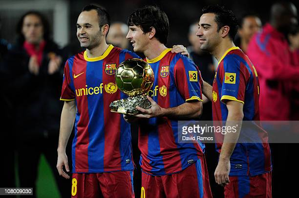 Lionel Messi of FC Barcelona holds the Ballon d'Or trophy flanked by his teammates Andres Iniesta and Xavi Hermandez prior the Copa del Rey quarter...