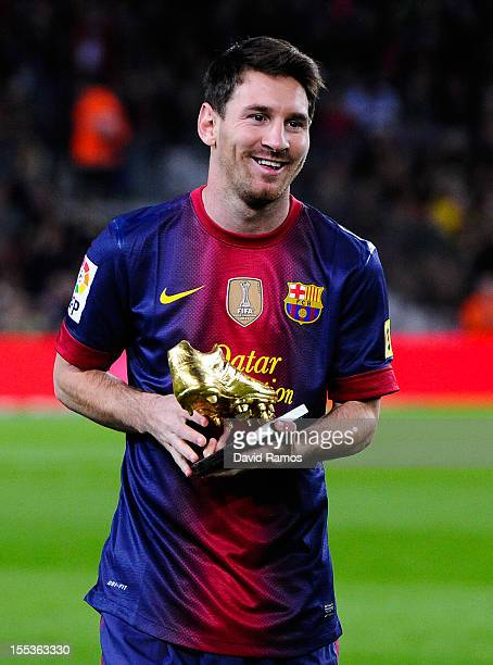 Lionel Messi of FC Barcelona holds the European Golden Boot 2012 trophy for the being the best scorer of the last season prior to the La Liga match...