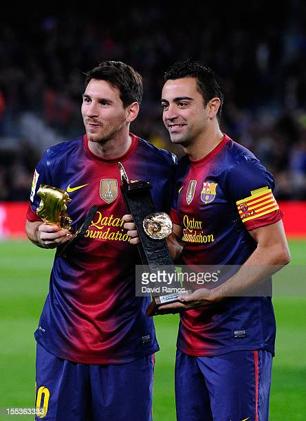 Lionel Messi of FC Barcelona holds the European Golden Boot 2012 trophy for the being the best scorer of the last season and Xavi Hernandez of FC...